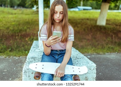 Teen girl 10-14 years old, sitting in hands of a skate. In summer city in casual jeans and pink T-shirt. Communication in Internet, in hands of smartphone holds writes message application.