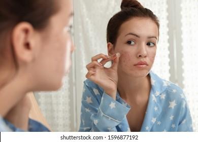 Teen girl applying acne healing patch near mirror in bathroom