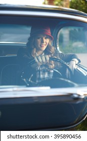 Teen girl behind the wheel of a classic American muscle car shot through the windshield with a vertical composition