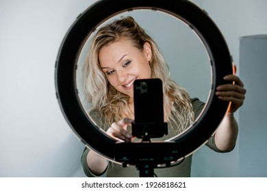 Teen girl blogger influencer recording video blog concept speaking looking at smartphone on tripod. Teenager social media vlogger shooting vlog, streaming online podcast on mobile phone.