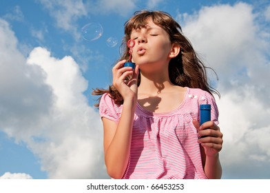 Teen girl blow bubbles, on background of the sky