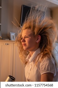 Teen girl blow dries her hair and the expressions on her face and hair blowing caught on camera