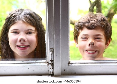 teen girl  and boy siblings with nose pressed against the window close up portrait