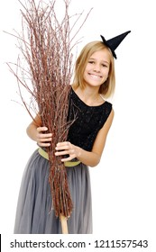 Teen girl with broom wearing a witch hat on Halloween.