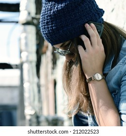 Teen girl calling smart phone outdoor. Teenage problem. Image toned and noise added.