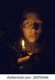 Teen girl with a candle, fear on her face