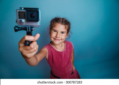 Teen girl child holding action camera smiling studio photo
