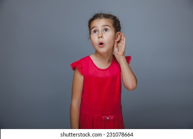 Teen girl child listens hand at the ear on gray background