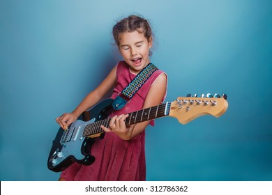 Teen girl child seven years, European appearance brunette in a pink dress plays a guitar and sings his eyes closed on a gray background, music, song