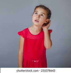Teen girl child's hand to his ear listening on a gray background