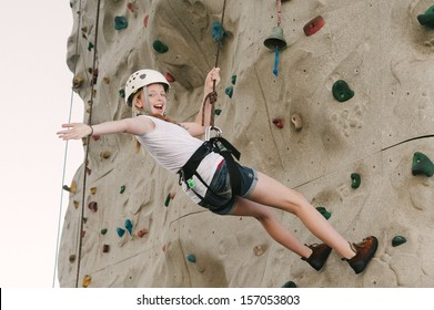 A teen girl climbing on a rock climbing wall with safety harness and helmet on.
