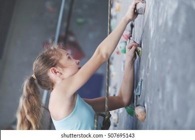 Teen girl climbing a rock wall indoor