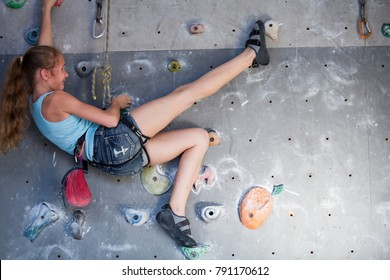 Teen girl climbing a rock wall indoor. Concept of sport life.