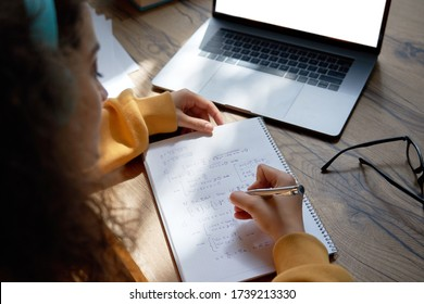 Teen girl college student wear headphones studying from home writing in workbook solving equations learning math sits at desk. Teenage school pupil learn online on laptop, close up over shoulder view.