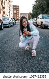Teen girl crouching on the street watching her cellphone