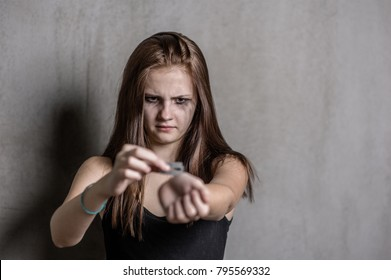 Teen girl  cuts veins on a hand on a dark background