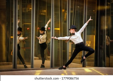 Teen girl dancing modern jazz among golden reflections in the mirror walls