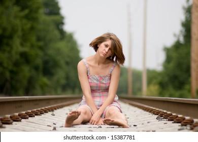 Teen girl depressed on railroad track