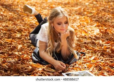 Teen girl with digital tablet lying on leaves