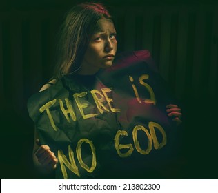 Teen girl with dirty face holding banner with a text - There is no God. Atheistic concept.
