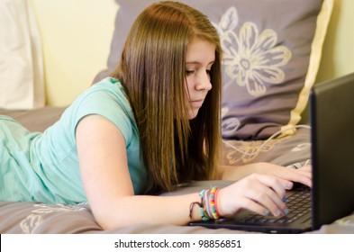 teen girl doing homework on a laptop