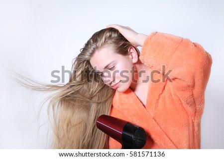 Teen girl drying long wet hair using hairdryer. Isolated on white  background in orange bathrobe 12ea79cf3