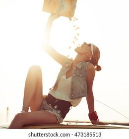 Teen girl eating chips outdoors