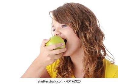 Teen girl eating green apple isolated on white background