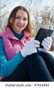 Teen girl with e-book reader in a park at winter time