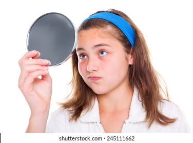 Teen girl examine her pimples in the mirror