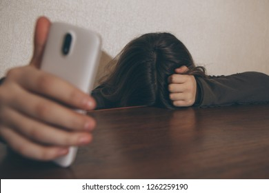 Teen girl excessively sitting at the phone at home. She is a victim of online bullying Stalker social networks - Image