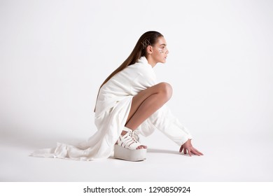 Teen girl in fashionable clothes posing in the studio. Fashion trend. Difficult Model Poses. Translation of words: cosmos, оn fire