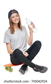 Teen girl in full length sitting on skate board holding a bottle of pure water isolated on white background