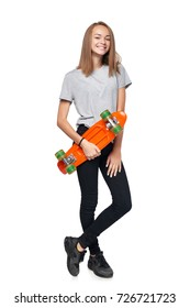 Teen girl in full length standing holding skate board smiling at camera, isolated on white background