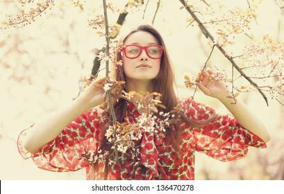 Teen girl in glasses near blossom tree