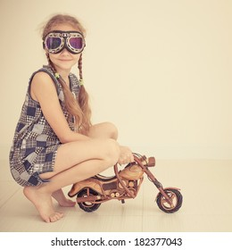 teen girl in glasses on toy motorcycle