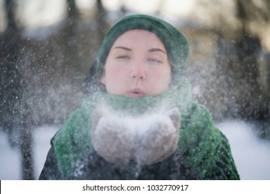 teen girl having fun blowing fresh snow from her hands