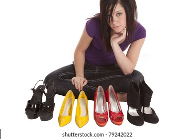 A teen girl is having a hard time trying to decide which shoes to wear.