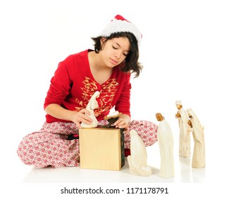A teen girl in her pajamas arranging the Nativity figures on the floor and a gift box before her.  On a white background.