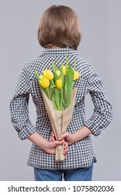 Teen girl hiding bunch of flowers behind itself, on gray background. Child with bouquet of yellow tulips as a gift. Happy mothers, Birthday or Valentines day.