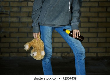 Teen girl holding a beer bottle and a teddy bear in the alley