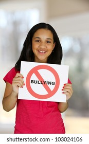 Teen girl holding a card that says no bullying