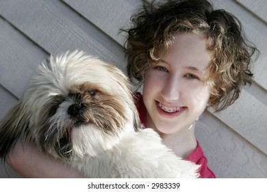 A teen girl holding her dog
