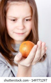 teen girl holding in the palm of mandarin