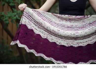 Ein Mädchen, das einen rosa-weißen Schal hält
