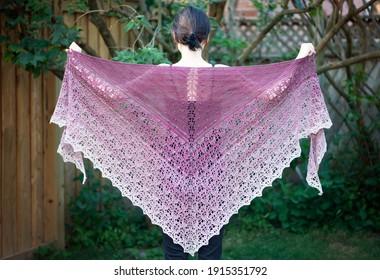 Ein kleines Mädchen, das einen hübschen, mauvinen Spitzen-Schal hochhält