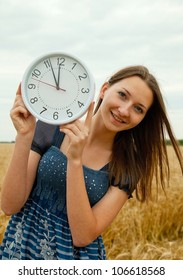 Teen girl holds watches staying outdoors