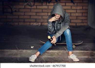 Teen girl in hood holding a beer bottle and smoking the cigarette on the steps in the alley