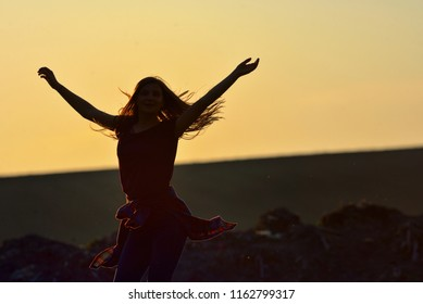 Teen girl jump against beautiful sunset on field