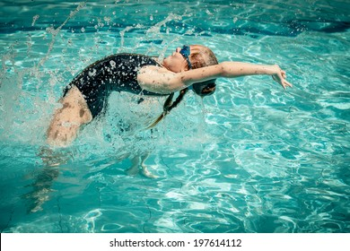 teen girl jumping in the swimming pool at the day time